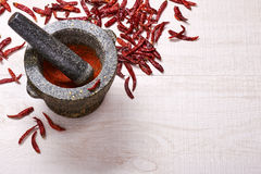 Pestle with mortar, surrounded by dried chili peppers Royalty Free Stock Photography