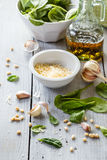 Pesto σπανακιού σε ένα βάζο γυαλιού, διακόσμηση: φύλλα σπανακιού, καρύδι πεύκων, παρμεζάνα τυριών, σκόρδο, ελαιόλαδο Στοκ εικόνα με δικαίωμα ελεύθερης χρήσης