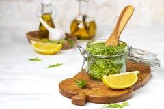 Pesto casalingo della rucola e del basilico in un barattolo di vetro immagini stock