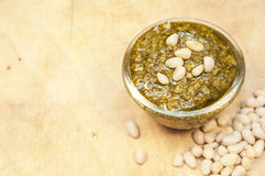 Pesto and cedar nuts on the wooden background Royalty Free Stock Photos