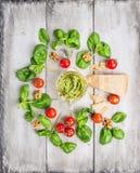 Pesto e ingredientes de la albahaca: parmesam, nueces, y tomates en la tabla de madera vieja blanca Imágenes de archivo libres de regalías
