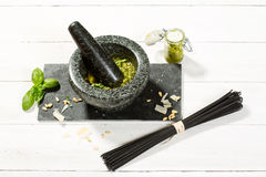 Pesto Genovese en mortier avec des ingrédients et des spaghetti noirs images stock