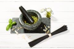 Pesto Genovese no almofariz com ingredientes e espaguetes pretos imagens de stock