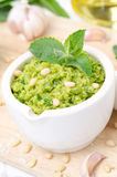 Pesto with green peas, mint and pine nuts, vertical close-up. Pesto with green peas, mint and pine nuts on a wooden board, vertical close-up Stock Photo