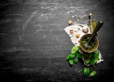Pesto i en mortel med vitlök och olivolja Arkivbild