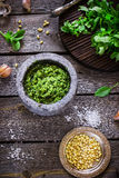 Pesto in marble mortar, salt, pine nuta and garlic on wooden table. stock photos