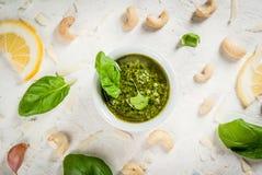 Pesto mit Bestandteilen auf einer weißen Tabelle Lizenzfreies Stockfoto