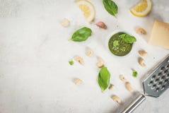 Pesto mit Bestandteilen auf einer weißen Tabelle Stockfotografie
