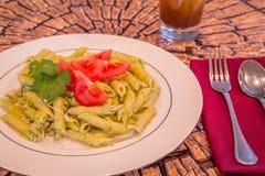Pesto penne makaron z świeżymi pomidorami i lukrową herbatą na drzewnego fiszorka tle Zdjęcia Royalty Free