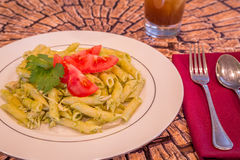 Pesto penne pasta with fresh tomatoes and iced tea on a tree stump background. Royalty Free Stock Photos