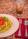 Pesto penne pasta with fresh tomatoes and iced tea on a tree stump background. Stock Images