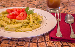 Pesto penne pasta with fresh tomatoes and iced tea on a tree stump background. Stock Photos