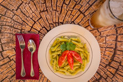 Pesto penne pasta with fresh tomatoes and iced tea on a tree stump background. Stock Image