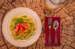 Pesto penne pasta with fresh tomatoes and iced tea on a tree stump background. Stock Photo