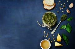 Pesto sauce and ingredient for pesto on the blackboard. Stock Photos