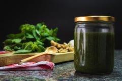 Pesto sauce jar with ingredients royalty free stock images