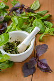 Pesto sauce in a mortar on a wooden background with basil leaves Royalty Free Stock Photography