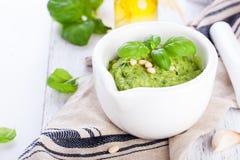 Pesto traditionnel fait maison de basilic avec l'huile d'olive, les écrous de cèdre et l'ail dans une cuvette blanche sur une tab Photographie stock