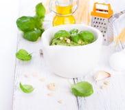 Pesto traditionnel fait maison de basilic avec l'huile d'olive, les écrous de cèdre et l'ail dans une cuvette blanche sur une tab Photographie stock libre de droits