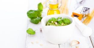 Pesto traditionnel fait maison de basilic avec l'huile d'olive, les écrous de cèdre et l'ail dans une cuvette blanche sur une tab Images stock