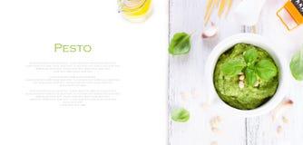 Pesto tradizionale casalingo del basilico con olio d'oliva, i dadi di cedro e l'aglio in una ciotola bianca su una tavola rustica Immagine Stock