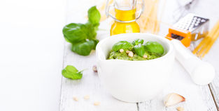 Pesto tradizionale casalingo del basilico con olio d'oliva, i dadi di cedro e l'aglio in una ciotola bianca su una tavola rustica Immagini Stock