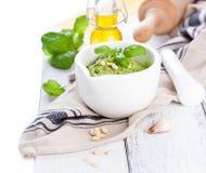 Pesto tradizionale casalingo del basilico con olio d'oliva, i dadi di cedro e l'aglio in una ciotola bianca su una tavola rustica Immagine Stock Libera da Diritti
