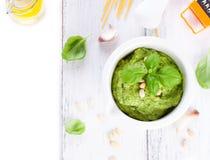 Pesto tradizionale casalingo del basilico con olio d'oliva, i dadi di cedro e l'aglio in una ciotola bianca su una tavola rustica Fotografia Stock Libera da Diritti