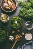 Pesto verde da couve no misturador no fundo rústico escuro com ingredientes, vista superior da mesa de cozinha Preparação do pest imagem de stock