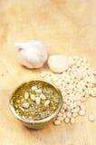 Pesto, vitlök- och cederträmuttrar på träbakgrund Arkivfoton