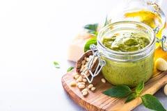 Pestosaus in glaskruik en ingrediënten Royalty-vrije Stock Afbeeldingen