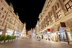 Pestsaule between illuminated buildings during night at Graben street in Vienna, Austria. One of many beautiful old buildings in the city of Vienna Royalty Free Stock Images