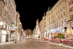 Pestsaule mellan upplysta byggnader under natt på den Graben gatan i Wien, Österrike Arkivfoto