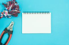 Pet accessories concept. Blank notebook with Rope, bowls. And rubber toy on blue background royalty free stock photos
