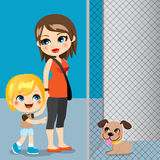 Pet Adoption. Little boy with mother adopting a cute dog from animal shelter Stock Images