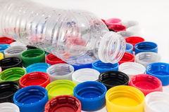 Pet bottle and many caps. Plastic bottle and many colored caps. Concept of recycle and reuse Royalty Free Stock Image