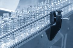 The PET bottles in the conveyor belt at drinking water factory. The drinking water filling machine manufacturing process royalty free stock image