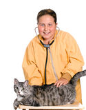 Pet Care. A young girl is using a stethoscope to listen to the heart of her pet cat, isolated against a white background Stock Image