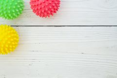 Pet care background. Pet care, veterinary, grooming concept. A white wooden background with a corner of pet toys - colorful rubber squeaky balls. Space for your Stock Images
