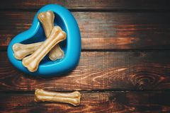 Pet care concept on dark wooden background. Delicious dog treats: chewing bones for dogs in a blue plastic heart-shaped bowl on a dark wooden background, top stock photography