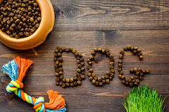 Pet care with dry food for pet - dog in plastic bowl on wooden background top view space for text Stock Photo