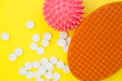 Pet care concept. Pet care items set- a rubber brush, a rubber squeaky ball and scattered pet vitamins, close up Stock Photography