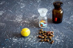 Pet cure concept. Pills and animal feed on grey stone background top view copyspace Stock Photos