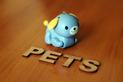 Pet dog. Wooden letters forming the words Pets with a robot dog Stock Photo