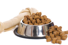 Pet Food. A dog bone and a bowl of dry food in a metal bowl, isolated against a white background Royalty Free Stock Photography