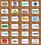 Pet food brands and logos. Collection of logos and brands of famous pet food companies on white tablet on rusty wooden background. brands like nutro, hills, iams Royalty Free Stock Images