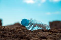 Pet a garrafa com água na areia do mar Foto de Stock Royalty Free