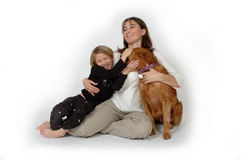 Pet Hugs. Woman and child on white background playing with a dog. Golden Retriever getting hugged by woman and child royalty free stock image