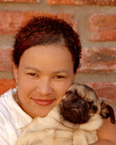 Pet lover. Outdoor portrait of a multiracial colored woman white smiling facial expression holding a little pug dog in her arms Stock Photo