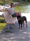 Pet and master. A man takes his rottweiler out for a walk, resting on a bench in front of the pond in the park Royalty Free Stock Photography